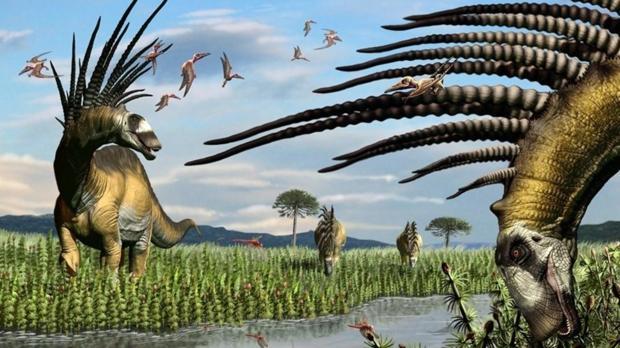 Un grupo de bajadasaurios a la vera de un curso de agua, en una vasta pradera de equisetos