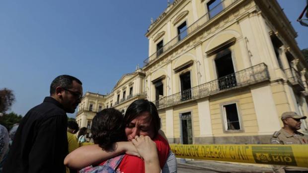 Dos funcionarias lloran ante la fachada del Museo Nacional de Río de Janeiro