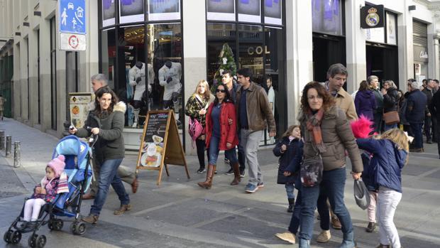 Varias personas pasean delante de la tienda del Real Madrid en Gran Vía, ayer por la mañana