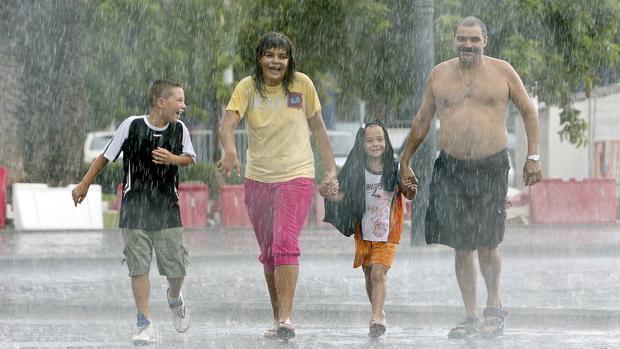 Imagen de una familia paseando bajo la tormenta cerca de la playa de La Malvarrosa de Valencia.
