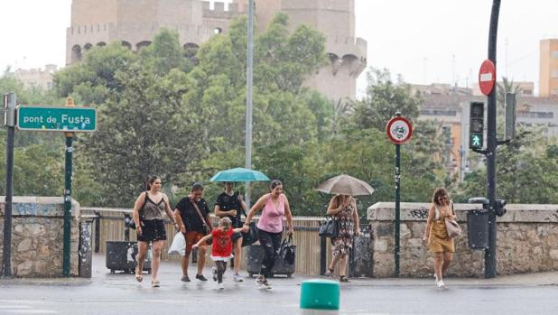 Transeúntes se protegen de la lluvia este lunes en Valencia