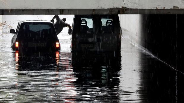 Una persona trata de salir de su coche, atrapado por las lluvias en Valencia
