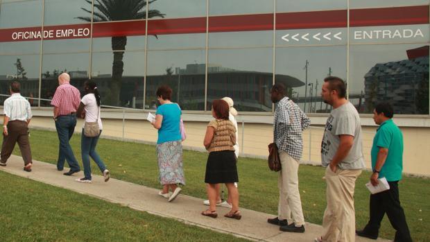 Trabajadores en paro, haciendo fila en una Oficina de Empleo