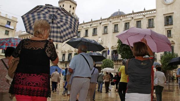 Espectadores de una procesión se protegen de la lluvia en la plaza del Ayuntamiento de Alicante