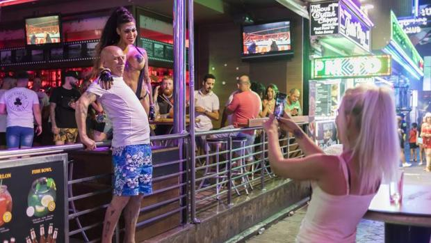 Un jubilado se fotografía junto a una gogó en topless en la calle Mallorca de Benidorm