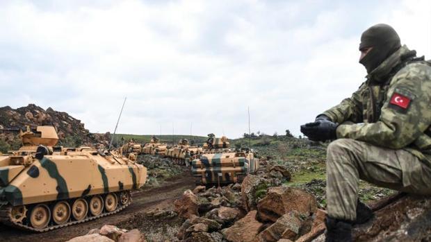 Un miembro del ejército turco junto a unos carros de comabte en la frontera con Siria