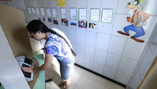Una funcionaria prepara una urna electrónica en Brasil