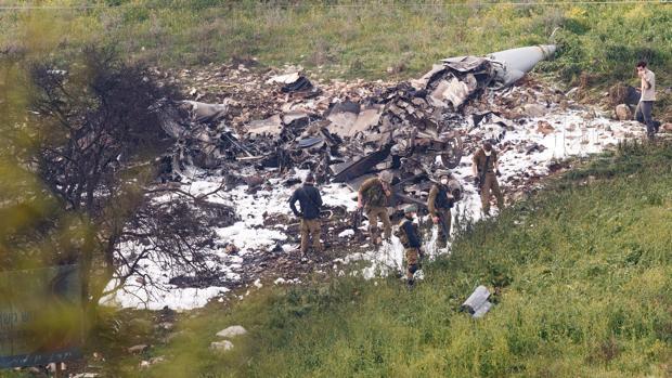 Soldados israelíes observan los restos de un avión F-16 del Ejército de Israel