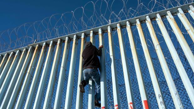 Un centroamericano escala por la valla que separa Estados Unidos y México en Tijuana
