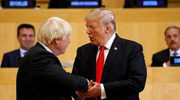 Trump estrecha la mano de Boris Johnson, durante un acto
