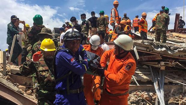 Los equipos de rescate sacan a una de las víctimas de entre los restos del edificio