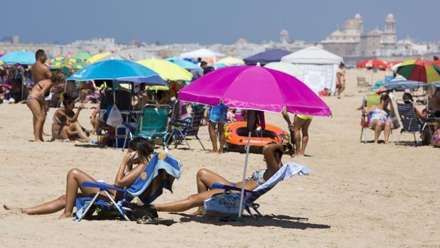 Dos personas tomanel sol en una playa de Cádiz.
