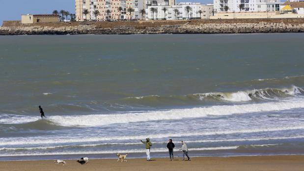 Gente en la playa con abrigos