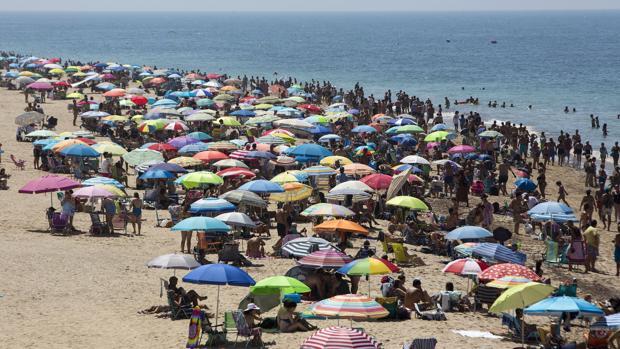 Playa gaditana repleta de bañistas durante un día de verano