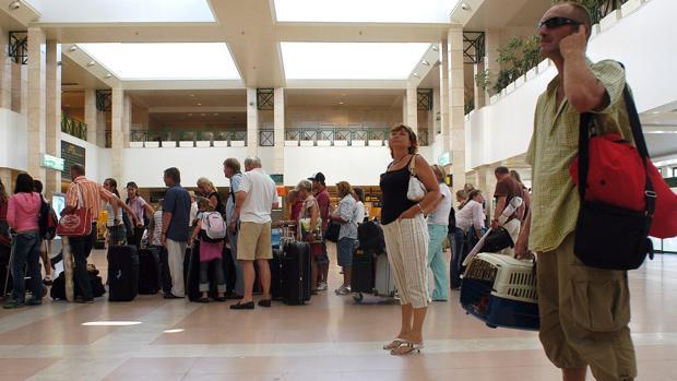 Turistas esperando para facturar sus maletas en el aeropuerto de Jerez.