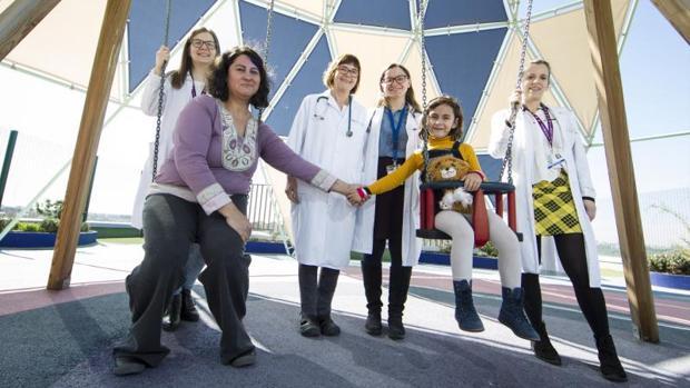 Cristina, acompañada de su madre, Helena Carpio, y el equipo que la trata en el Hospital 12 de Octubre