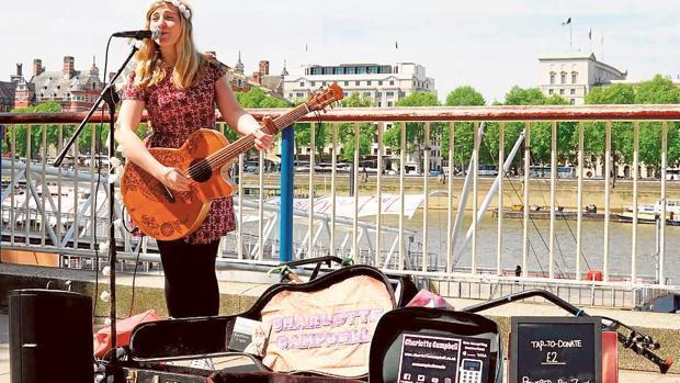 Una chica realiza una actuación musical callejera