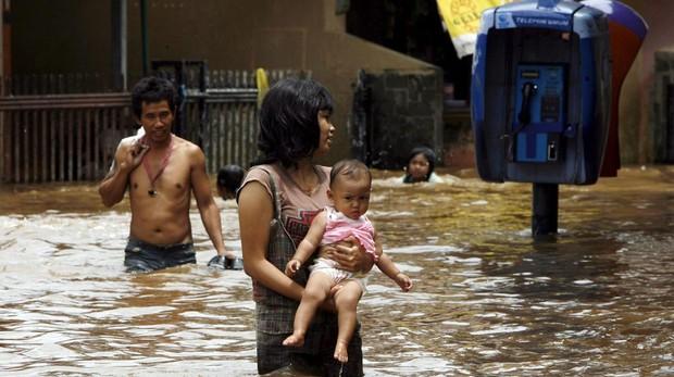 Fotografía del 6 de febrero de 2018, de varios residentes que caminan por una calle inundada por las aguas del río Ciliwung en Yakarta (Indonesia). Según informes oficiales, la parte noroeste de Yakarta se hunde a una velocidad de entre siete y 10 centímetros por año, lo que la convierte en una de las ciudades de más rápido hundimiento del mundo