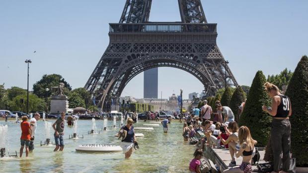 Multitud de personas se refrescan en las fuentes de los jardines del Trocadero junto a la Torre Eiffel en París este viernes