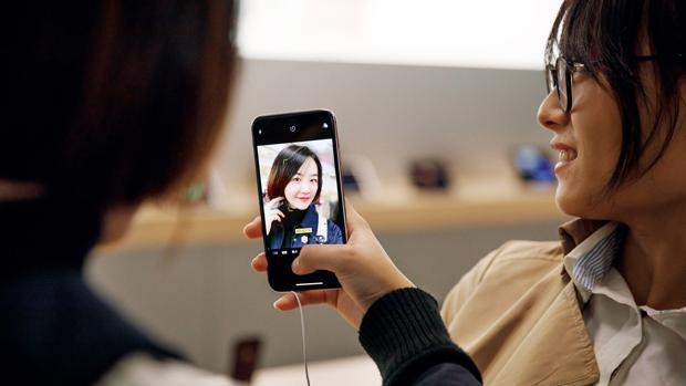 Una joven se hace un «selfie» en una App Store de Shanghai con un iPhone X